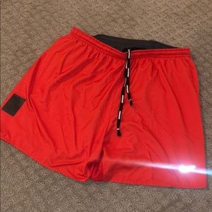 Orange/red Nike running shorts